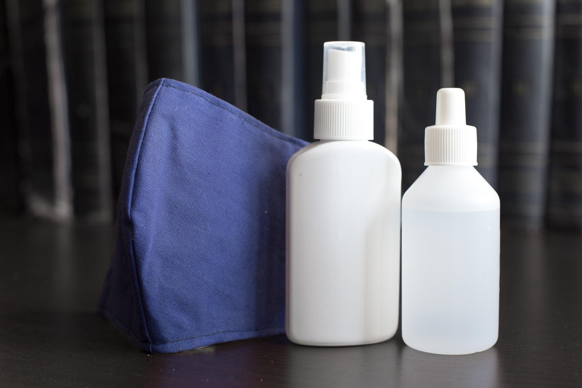 Twee flessen met schoonmaakspray en een schoonmaakdoek.